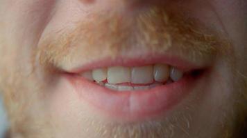 primo piano estremo della bocca di un uomo che cambia forma per sorridere