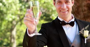 sposo felice sorridendo alla telecamera e brindando con champagne