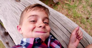 Cute little boy en el parque sonriendo y mirando a la cámara