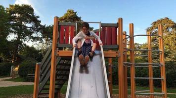 niño y niña jugando en el tobogán del patio video