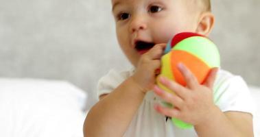 Linda niña jugando con pelota suave en la cama