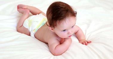 bambino in pannolino sdraiato sul letto