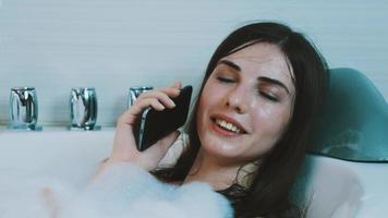 menina morena tomando um banho cheio de espuma. falando no telefone. relaxar. rir. sorriso