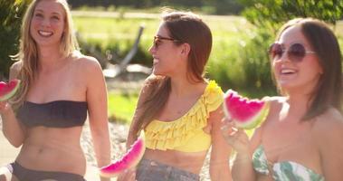 ragazze che ridono e mangiano anguria accanto a una piscina video