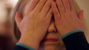 Close up of a cute little girl saying peek-a-boo and then covering her face