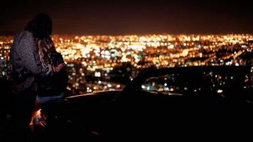 Young couple hugging and looking at night city lightsnext to a convertible video