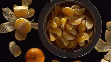 un cuenco de mandarinas sobre una mesa negra.