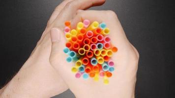 Mensch legt viele Farbtuben auf ein Glas mit einem Orangensaft auf einen schwarzen Tisch (Draufsicht) video
