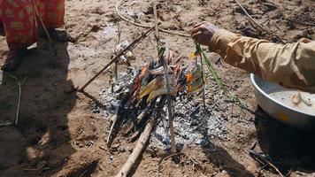 Hombre agregando peces en un bambú dividido colocado sobre fuego abierto