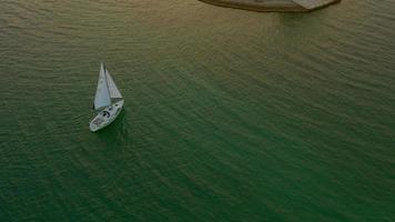 4k aérea: barco à vela perto da ilha