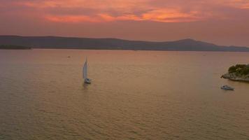4k aérea: barco à vela flutuante ao pôr do sol