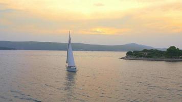 4k aérea: barco à vela ao pôr do sol