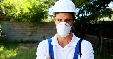 trabajador sonriente de pie con los brazos cruzados