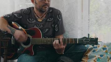 homem tocar guitarra no terraço da casa de campo. garota na mesa com bebidas. em repouso