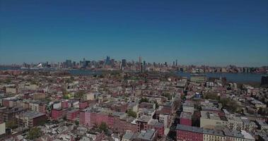 Hoboken NJ volar vista hacia atrás de edificios con Manhattan en tiro