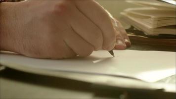 uomo che scrive sulla carta con la penna