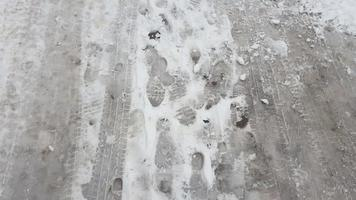 Treads and footprints in snow, city street covered in snow. video