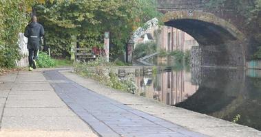 corredor correndo sob a ponte ao lado do canal do regente video