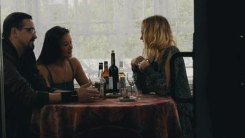 garota bate-papo com o casal à mesa com bebidas no terraço da casa de campo. amigos