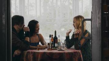 duas meninas e um homem conversando à mesa com bebidas no terraço de uma casa de campo