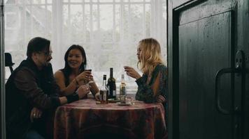 duas meninas e um homem conversando à mesa. beber álcool no terraço de casa de campo
