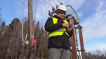 engenheiro eletricista usando tablet perto de linhas de energia e transformador video