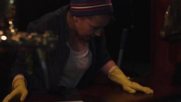 scrubwoman in guanti accendere la musica in un club vuoto, cantare nel microfono sul palco