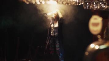 scrubwoman in guanti canta sul palco nel microfono vintage sotto i riflettori. Fumo