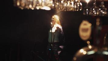 scrubwoman in guanti danza cantare sul palco nel microfono vintage sotto i riflettori