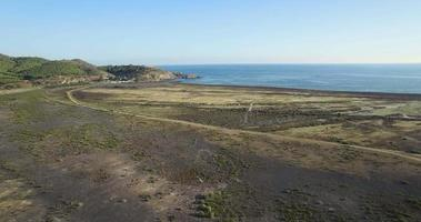 Aerial semi-desertic coast wit a car crossing