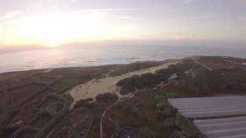 vista aérea sobre dunas de areia de grama do oceano ao nascer do sol com o oceano ao fundo - praia de santa cruz, torres vedras, portugal