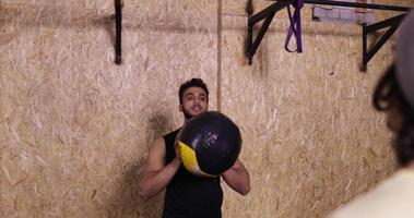 Deux homme dans la salle de sport sport exercice lancer la formation de gymnastique de balle, jeune sportif travaillant
