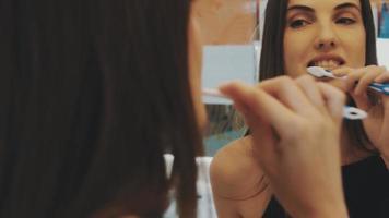 ragazza bruna spazzolare i denti davanti allo specchio in bagno. riflessione. igiene