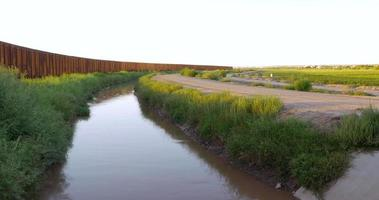 un fiume e una grande recinzione metallica si estendono all'orizzonte video