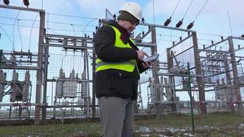engenheiro eletricista tira fotos com tablet perto da subestação no inverno video
