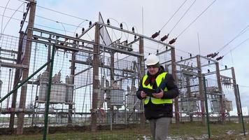 engenheiro eletricista escrevendo perto da subestação
