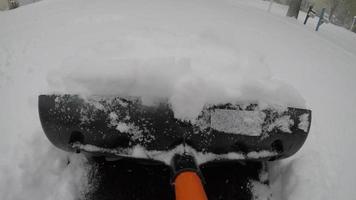 pov empurrando neve fresca com uma pá na calçada