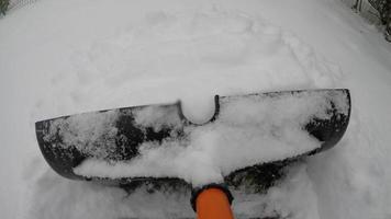 pá de neve pov na passarela de tijolos empurrando neve