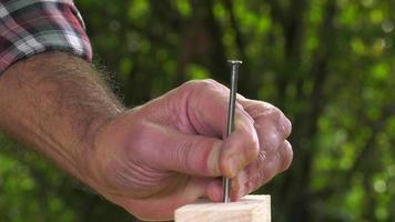 carpentiere che inchioda una punta con un martello
