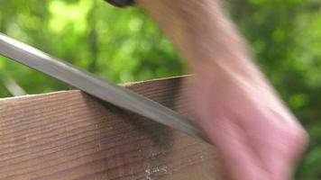 usando una raspa per legno sul bordo di una tavola