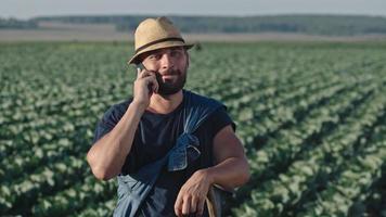agriculteur parlant au téléphone sur terrain