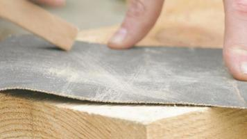 lucidatura di assi di legno con carta vetrata