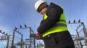 engenheiro eletricista usando tablet perto da subestação e indo embora video