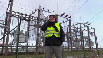 Ingeniero electricista hablando por teléfono inteligente cerca de la subestación en invierno video