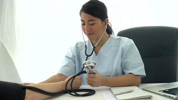 junger asiatischer Arzt, der den Blutdruck misst