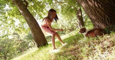 linda garota multiétnica brincando com seu cachorrinho em um parque