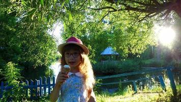 petite fille aux cheveux longs mange de la glace dans le parc.