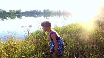 niña se encuentra en la orilla de un gran lago. ve una mariposa sobre la hierba. amanecer en el lago.