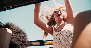 adolescente loira em pé e acenando alegremente na viagem