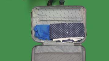 Packen eines Koffers auf grünem Bildschirm